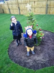 Children posing with a christmas tree